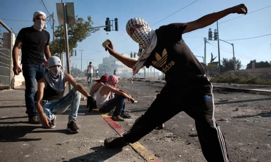 A Palestinian boy hurls stones at Israeli police during the second day of clashes in Shu'afat after the kidnapping and murder of Mohammad Abu Khdeir.