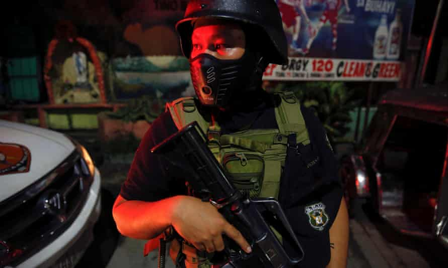 A member of the Philippines special police force stands guard in a street in Manila