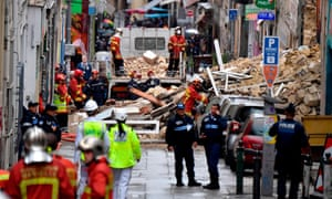 Police and firefighters begin clearance work at the site where two buildings collapsed in Marseille on Monday
