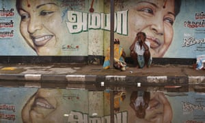 A couple sits along a flooded road under a picture of Jayalalithaa, chief minister of Tamil Nadu