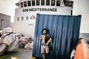 Aloys Vimard, a project coordinator for MSF, plays an accordion on the bow of the Aquarius