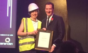 Theresa May appeared to mock George Osborne by accepting an award from the former chancellor wearing a hi-vis jacket and hard hat.