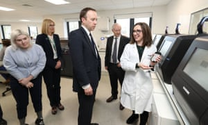 The health secretary, Matt Hancock, is shown a demonstration of a blood testing machine in operation during a visit to Randox in County Antrim