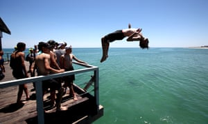 A teenager leaps from the Henley beach jetty in Adelaide. Maximum temperatures in the city are forecast to stay above 35C until at least Saturday.