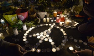 """People form the Pray for Paris logo with candles near the """"Belle Equipe"""" cafe on rue de Charonne in Paris on November 20, 2015."""