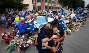 A softball team hugs after paying their respects at a makeshift memorial at Dallas police headquarters