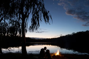 Sharing a sunset with her dog, fox by the campfire at stannary hills dam, Queensland.
