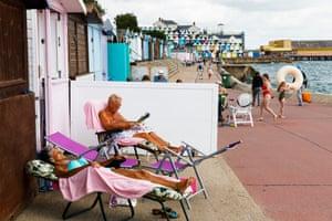 People sitting outside  a beach hut