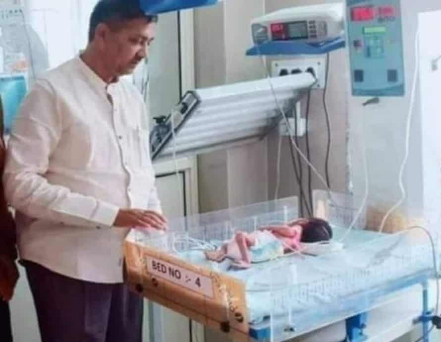 Local politician Rajesh Mishra with the newborn girl who was found after being buried alive.