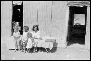Shirley Murray with three children outside a shack at Moree. People had to build their own houses with whatever they could find