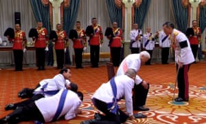 Thai prime minister Prayuth Chan-Ocha (centre), privy council president General Prem Tinsulanonda (seated) and others prostrate themselves in front of newly appointed Thai King Maha Vajiralongkorn.
