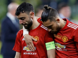 Manchester United's Bruno Fernandes is consoled by Alex Telles.