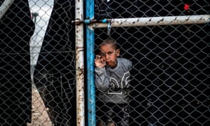 A child behind a wire fence in the al-Hawl refugee camp in Syria