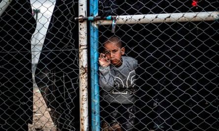A child behind a wire fence door in al-Hawl camp in Syria, which houses relatives of Islamic State fighters, including Australians.