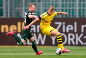 Dortmund's wunderkind Erling Braut Haaland controls the ball as to Wolfsburg's Maximilian Arnoldlooks on.