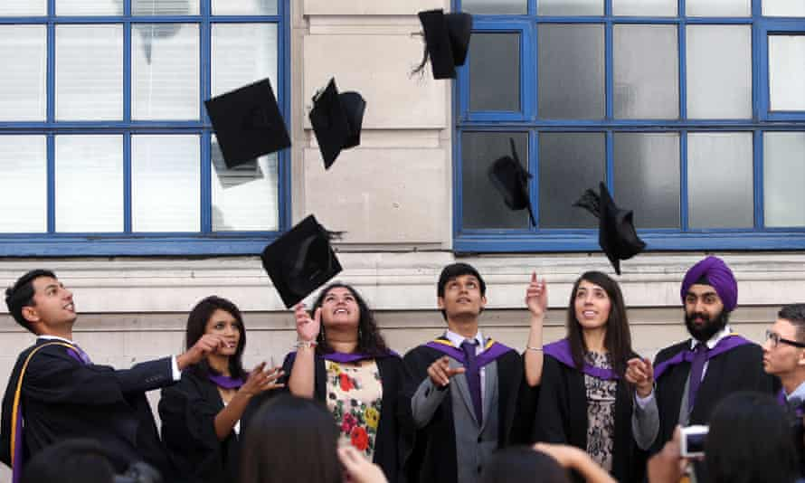 University students throw mortarboards in the air