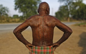 Jhingur Ram, 76, a follower of Ramnami Samaj, who has tattooed the name of the Hindu god Ram on his entire body, outside his house in the village of Chandai.