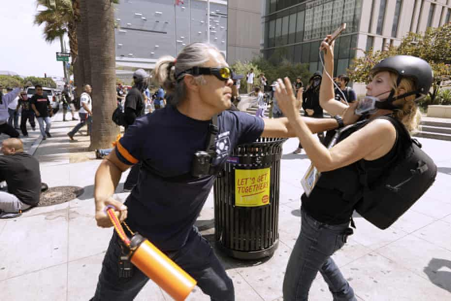 An anti-vaccine protester, left, attacks journalist Tina Desiree Berg in front of the Los Angeles police department headquarters on 14 August.