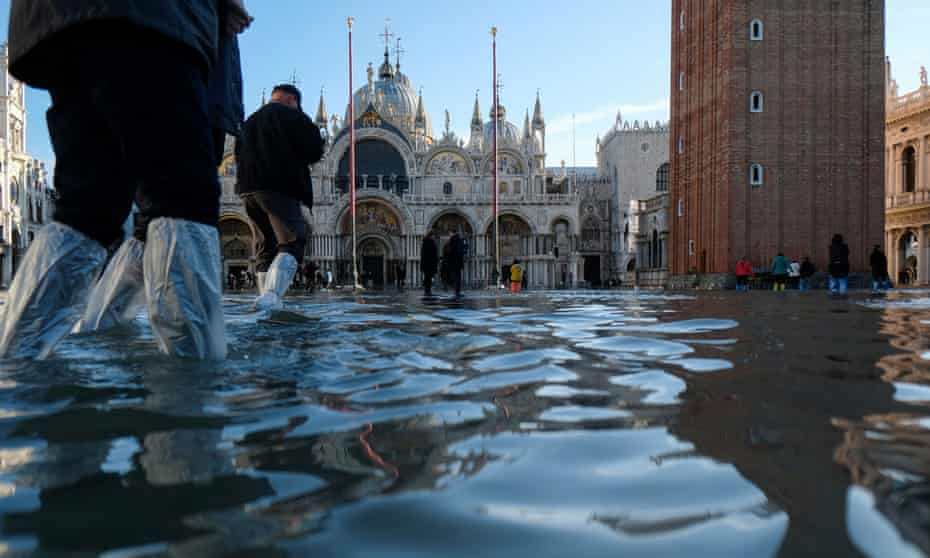 Tourists walk in the flooded St Mark's Square
