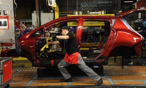 An employee works on a car production line