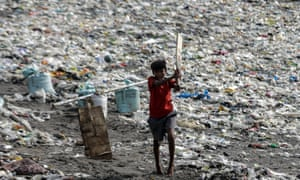 A boy plays cricket at a beach covered with plastic waste, in Mumbai, India