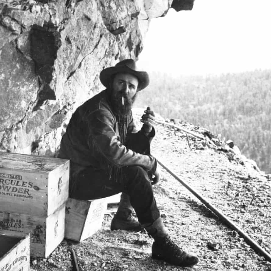 Sculptor Korczak Ziolkowski in 1950 on the side of the mountain sitting, smoking, near boxes of dynamite