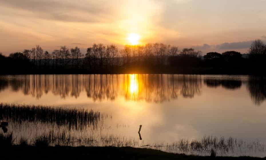 A beautiful sunset reflecting over a lake along the Ystwyth trail