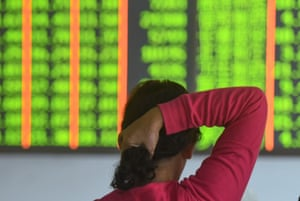 A investor monitors stock prices at a securities company in Hangzhou, China, as stocks plunged almost 3% today.