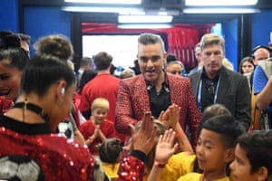 Robbie greets mascots following his performance in the opening ceremony