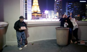 Joe, who is homeless, holds a sign asking for help as tourists take a selfie on the Strip in Las Vegas.