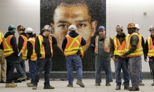 Construction workers stand in front of a mosaic by Chuck Close at the new 86th Street station.