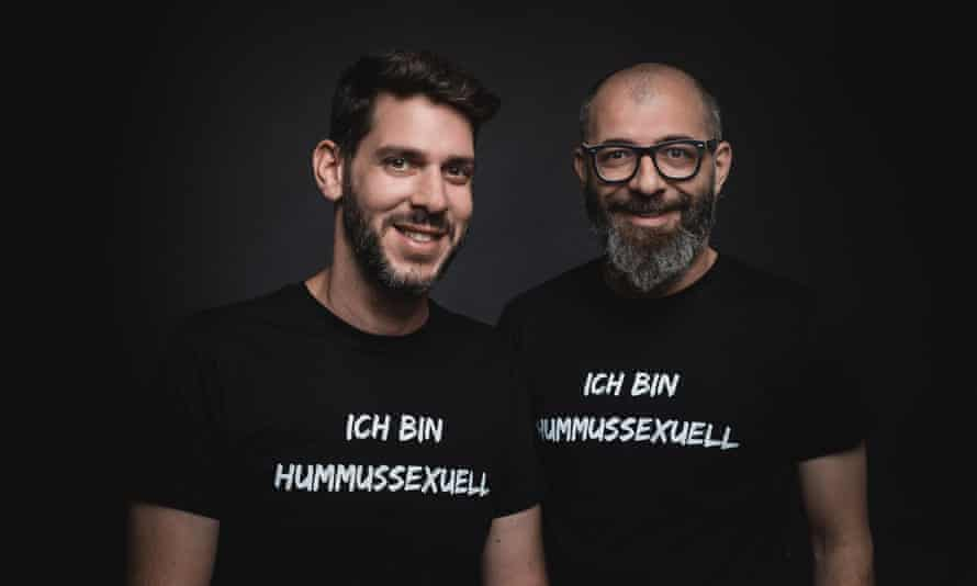 Oz Ben David and Jalil Dabit, standing side by side and smiling and both wearing black t-shirts saying 'ich bin hummussexuell'
