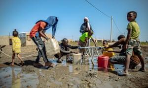Refugees fill water bottles in Village 8 refugee settlement in Eastern Sudan.