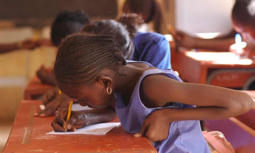 African pupils sitting at their wooden desk in the classroom.