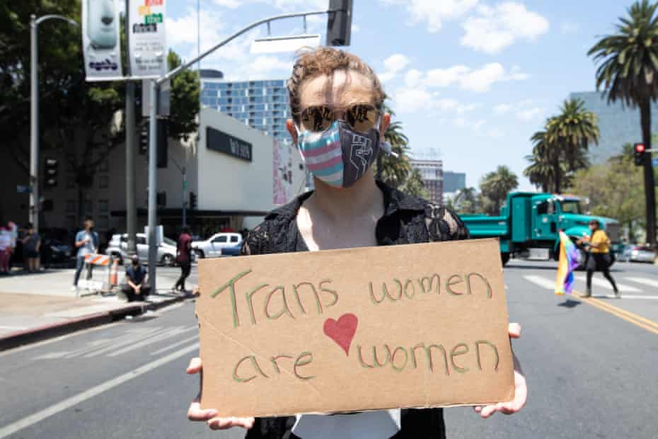 """A counter protester at Wi Spa on 3 July holds a sign that says """"Trans women are women."""""""