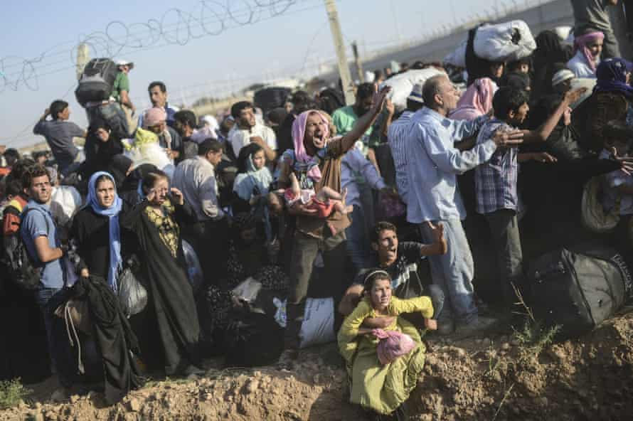 Syrian refugees pass through broken border fences and trenches to enter Turkey.