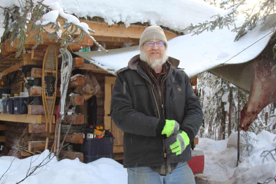 Glenn Helkenn outside his small log cabin on the outskirts of Fairbanks.