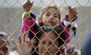 Daniela Fernanda Portillo Burgos sits on the shoulders of her mother, Iris Jamilet, 39, as they look out through the fence of a immigrant shelter in Piedras Negras.