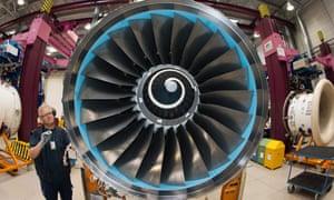 A Rolls-Royce employee works on a plane engine.