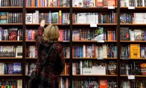 A woman takes a book off the shelf in a bookshop