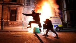 A demonstrator skateboards in front of a burning police vehicle.