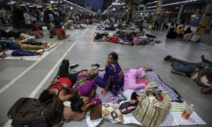 Stranded passengers rest inside a railway station after trains between Kolkata and Odisha were cancelled ahead of Cyclone Fani.