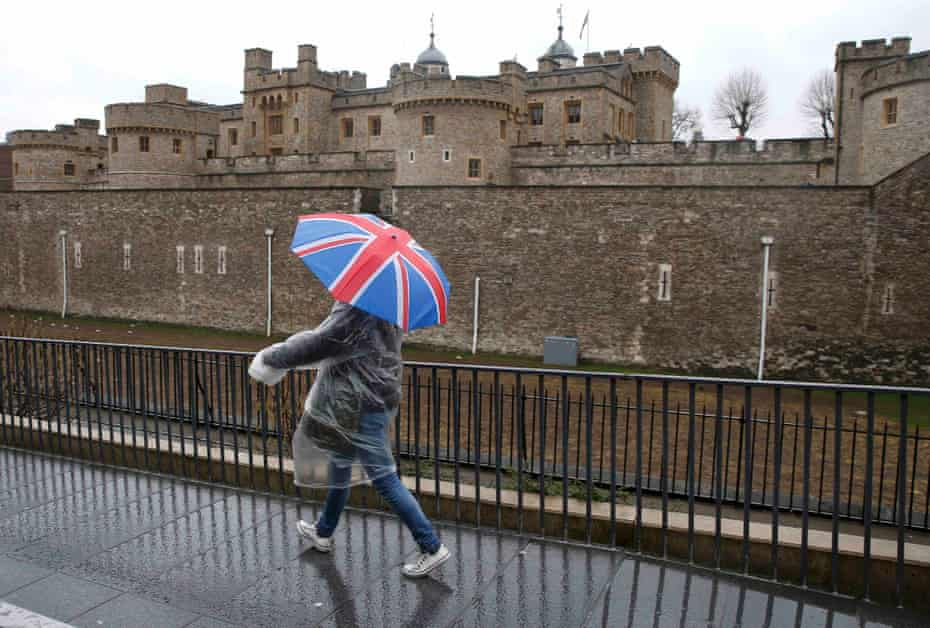 A tourist carrying a Union Flag umbrella passes the Tower of London.