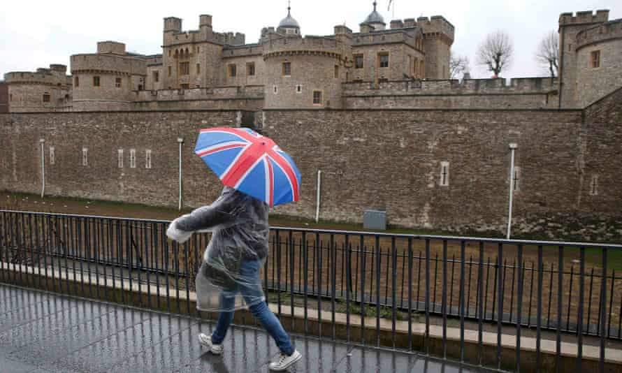 A man sheltering under a union jack umbrella walks past the Tower of London