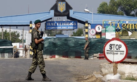 A Ukrainian soldier stands guard at a checkpoint ib the Russian border.
