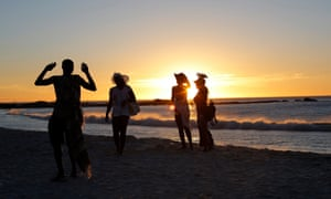 Beach goers are silhoutted against the sun as its sets for the last time for 2014 in Camps Bay, Cape Town, South Africa, 31 December 2014.