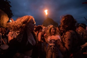 People dance as they gather at Avebury Neolithic henge monument after sunset