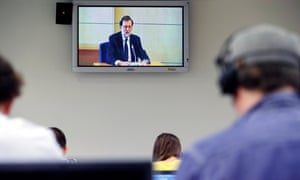 Journalists watch a monitor displaying the Spanish prime minister, Mariano Rajoy, as he testifies at the national court in San Fernando de Henares.