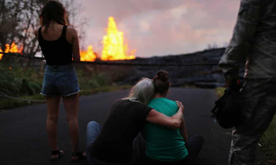 Residents watch lava erupting from a Kilauea volcano fissure in Leilani Estates, on Hawaii's Big Island, on 23 May 2018 in Pahoa, Hawaii.