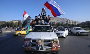 Syrian government supporters wave Syrian, Iranian and Russian flags as they chant slogans against U.S. President Trump during demonstrations following a wave of U.S., British and French military strikes